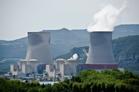Nuclear plant generating electricity. Two towers among hills