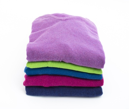 Stack of colorful wool or cashmere sweaters isolated on white photo
