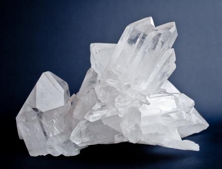Large crystals of white quartz on dark blue background Stock Photo