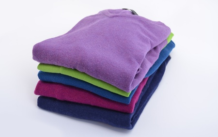 Pile of colorful, folded cashmere or merino wool jumpers isolated on white