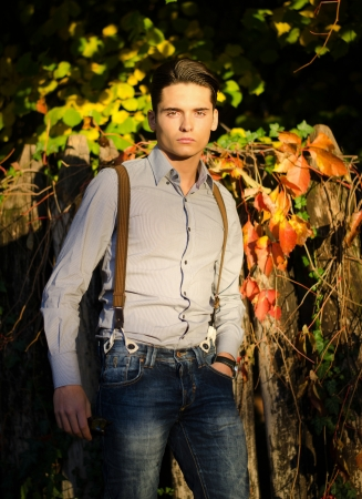 Attractive young male model outdoors in nature in beautiful sunset light
