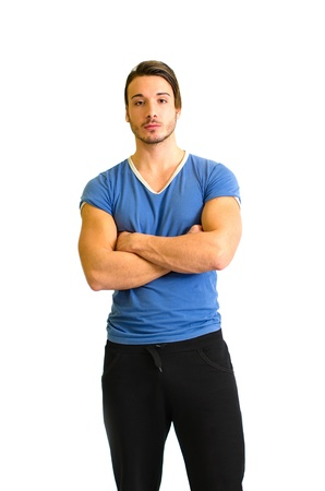 Handsome and athletic guy standing with arms crossed on his chest photo