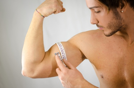 Athletic young man measuring biceps with tape meter photo