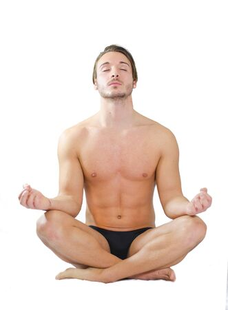 Fit and muscular young man in meditation, lotus position, isolated on white background photo