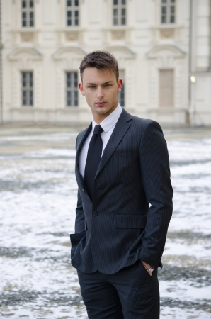 Good looking young man in suit, elegant palace with snow on the ground photo