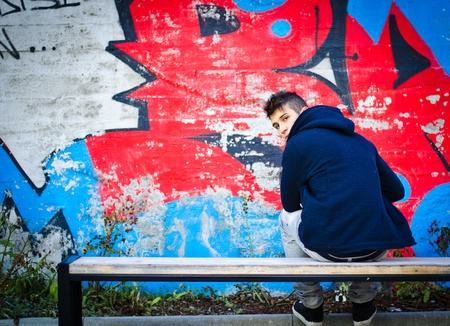 Young man with hoodie sitting on bench in front of graffiti wall photo