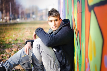 Handsome young man sitting on ground against colorful graffiti covered wall