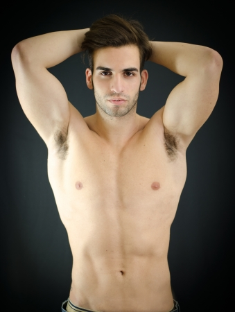 Sexy shirtless young man with arms up behind his head, showing muscular torso, pecs and abs