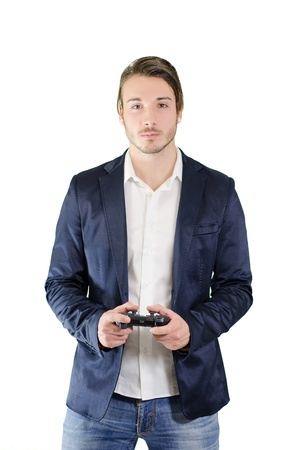 Young man playing videogames with joypad or joystick, standing and isolated on white photo