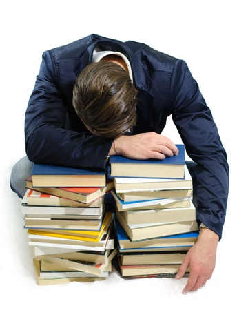 Young student sleeping on piles of books, isolated on white Stock Photo - 19377578