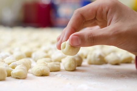 Closeup of hand making traditional homemade italian gnocchi pasta photo