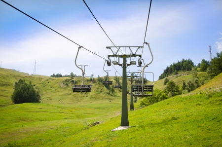 no snow: Emtpy chairlift in ski resort. Shot in summer with green grass and no snow Stock Photo
