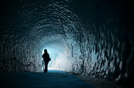 cavern: Human figure silhouette inside ice cave under glacier in Chamonix, France Stock Photo