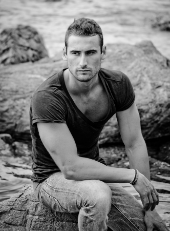 Black and white portrait  of attractive and athletic young man sitting on a rock by the sea photo