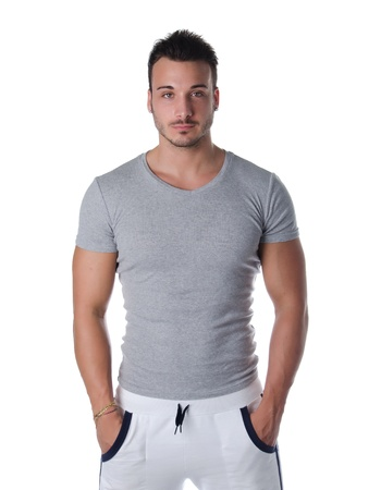 muscular man: Athletic and handsome young man standing confident with hands in his pockets, isolated on white Stock Photo