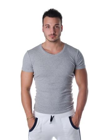young man standing: Atletico e bel giovane uomo in piedi fiducioso con le mani in tasca, isolato su bianco