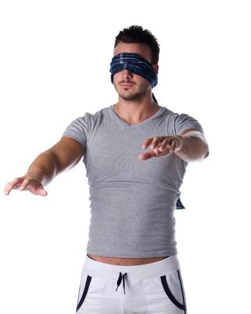 ojos vendados: Hombre joven con los ojos vendados a tientas en la oscuridad, el concepto de confusi�n, crisis, problema o desaf�o Foto de archivo