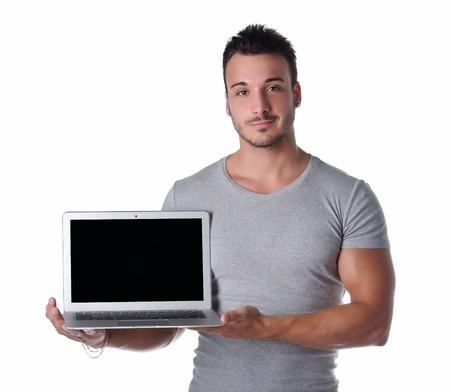 Atractiva joven sosteniendo y mostrando ordenador port?til con pantalla en blanco, aislado en blanco