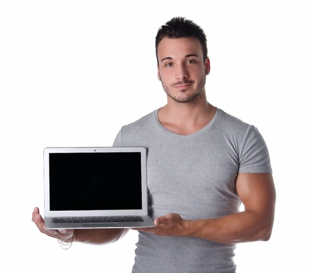 exhibiting: Attractive young man holding and showing laptop computer with blank screen, isolated on white