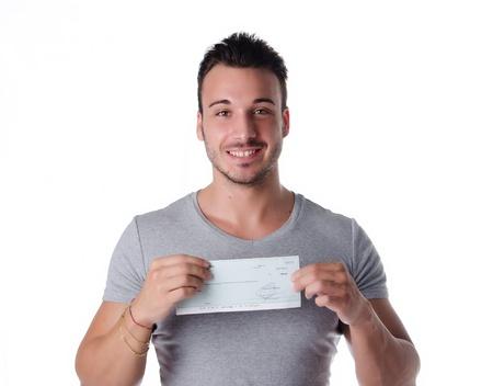 Gelukkig, lachende jonge man met een cheque (check) in handen, kijken naar de camera