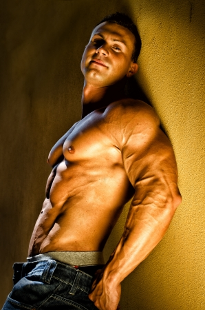 naked abs: Attractive and muscular male bodybuilder leaning against yellow wall smiling Stock Photo