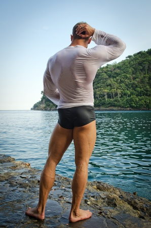 muscle shirt: Muscular bodybuilder facing the sea, seen from the back wearing wet shirt Stock Photo