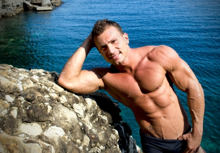 Smiling, attractive young bodybuilder shirtless by a sea rock photo