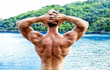 Muscular bodybuilder facing the sea with hands behind his head showing back, shoulders and arms photo