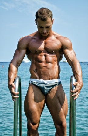 Handsome young bodybuilder getting out of sea or ocean water looking at his muscular torso, pecs, arms and abs photo