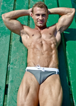 beach hunk: Muscular and fit young bodybuilder laying down on green wood planks Stock Photo
