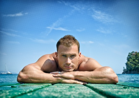 Muscular and handsome young man resting his chin on his hands, laying on wood planks looking at camera photo