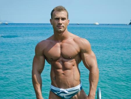 musculos: Apuesto joven fisicoculturista de pie con vistas al mar o al océano detrás mostrando torso muscular, pectorales, brazos y abdominales