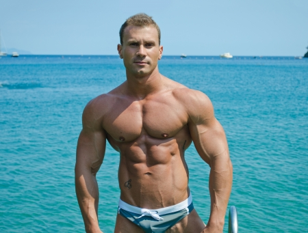 fit: Handsome young bodybuilder standing with sea or ocean behind showing muscular torso, pecs, arms and abs Stock Photo