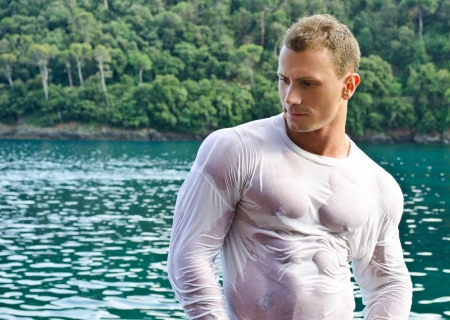 Attractive young bodybuilder by the sea with wet shirt on, serious expression