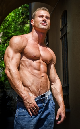 Attractive and muscular male bodybuilder shirtless in jeans smiling