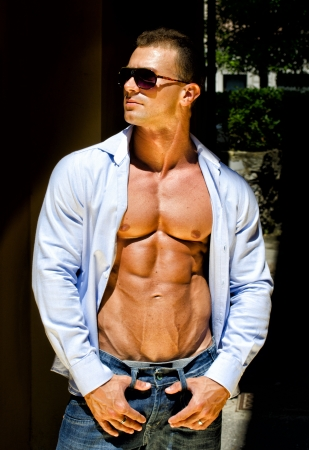 Attractive young muscle man outdoors with shirt open, showing muscular pecs, abs,and torso