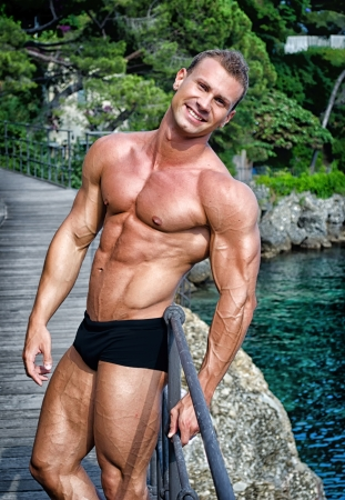 Smiling young bodybuilder standing with sea or ocean behind showing muscular torso, pecs, arms and abs photo