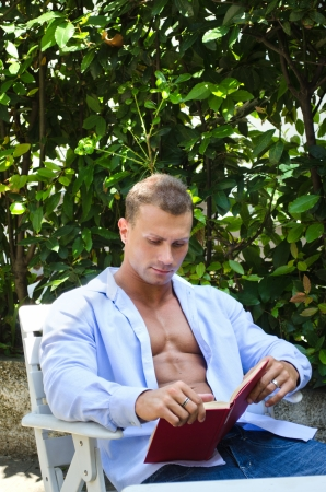 Handsome athletic young man reading book outside with shirt open showing muscular pecs and abs Stock Photo