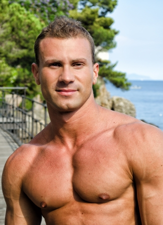 pecs: Handsome young muscle man smiling, outdoors, showing muscular pecs and torso Stock Photo