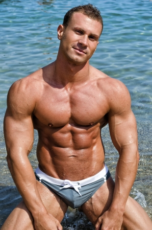 Smiling, attractive young bodybuilder shirtless in bathing suit kneeling on the beach photo