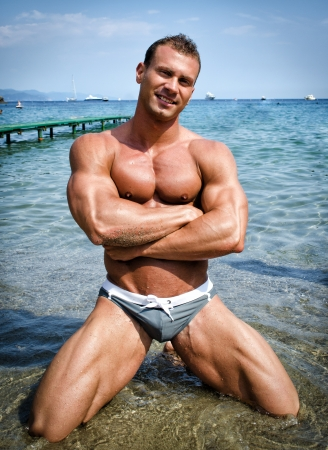 Smiling, attractive young bodybuilder shirtless kneeling in the sea water photo