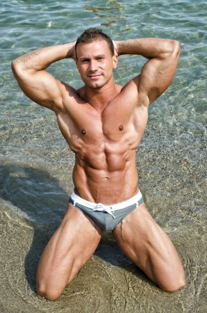Attractive and fit young bodybuilder in bathing suit kneeling on the beach photo