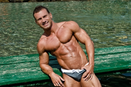 pecs: Muscular and fit young bodybuilder leaning on green wood planks on the sea Stock Photo