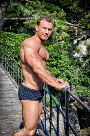 Handsome young bodybuilder outdoors by metal railing, profile photo photo