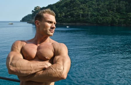 Attractive muscular young man with arms crossed and sea or ocean behind, large copyspace photo