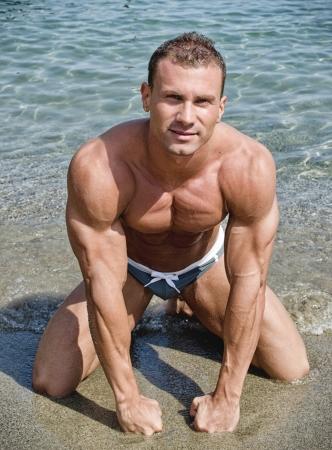 desnudo masculino: Culturista joven hermoso de rodillas en la arena de la playa, con los pu�os en el suelo
