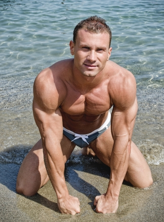 naked abs: Handsome young bodybuilder on his knees on the beach sand, with fists on the ground Stock Photo