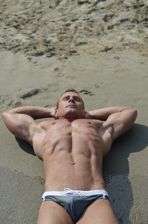 Handsome young bodybuilder resting on beach sand, large copyspace above photo