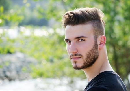 カメラで見て魅力的な若い男、屋外の肖像画