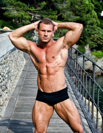 Attractive young muscle man smiling, outdoors, showing muscular body with hands behind his head photo